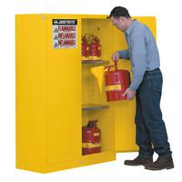Flammable Storage Cabinet being filled by man with flammable canisters.